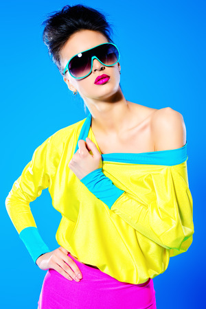 eyewear fashion: Glamorous fashion model posing in vivid colourful clothes and sunglasses. Bright fashion. Optics, eyewear. Studio shot.
