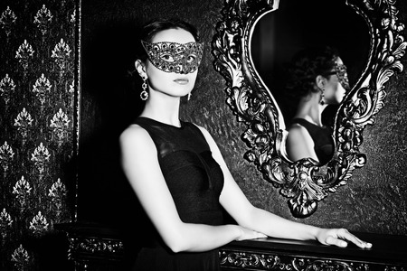 black mask: Beautiful mysterious stranger girl in venetian mask. Carnival, masquerade. Jewellery, gems. Stock Photo