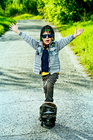 freetime activity: Cool 7 year old boy with his skateboard on the street. Childhood. Summertime.