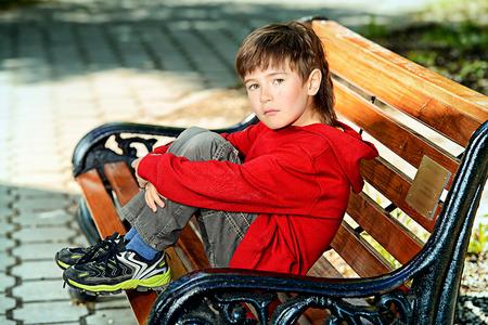 sadly: Ritratto di un ragazzo seduto su una panchina e purtroppo guardando in lontananza. Giorno d'estate.