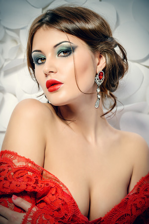 ladies bust: Seductive sensual woman in elegant red suit on a background of white flowers. Beauty, fashion.