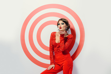 jumpsuit: Magnificent young woman in bright red suit posing on a red target. Beauty, fashion. Isolated over white. Stock Photo