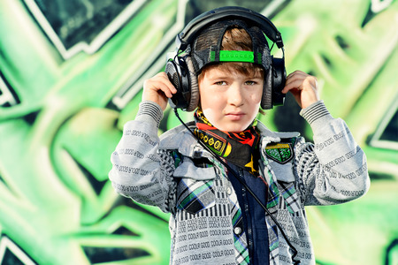7 year old: Trendy 7 year old boy on the street. Graffiti background. Modern generation. Stock Photo