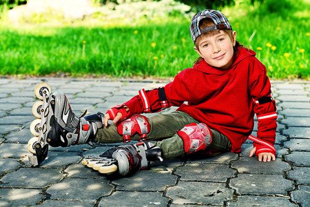 7 year old: Cool 7 year old boy rollerblades on the street. Childhood. Summertime.