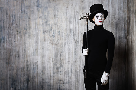 Elegant expressive male mime artist posing with walking stick by a grunge wall. Stock Photo