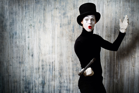 dramatic characters: Elegant expressive male mime artist posing with walking stick by a grunge wall. Stock Photo