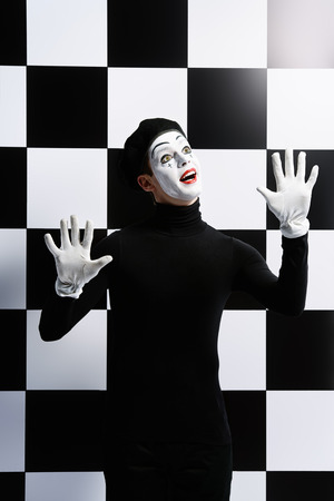mime: Professional mime artist performing different emotions. Chess board background. Stock Photo