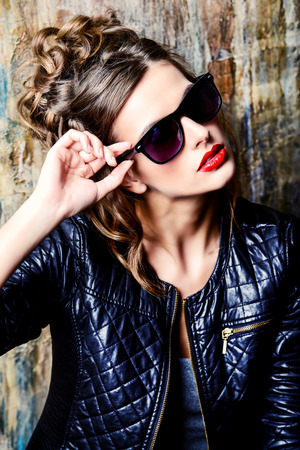 attractive gorgeous: Fashion shot of a gorgeous young woman wearing black leather jacket and sunglasses. Stock Photo