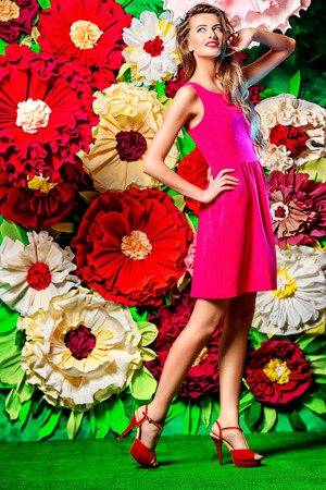womanly: Full length portrait of a beautiful happy young woman posing on a background of bright large flowers. Beauty, fashion. Summer inspiration.
