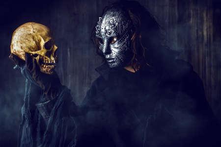 mystery: Mysterious man in iron mask holding skull. Steampunk. Fantasy. Halloween.
