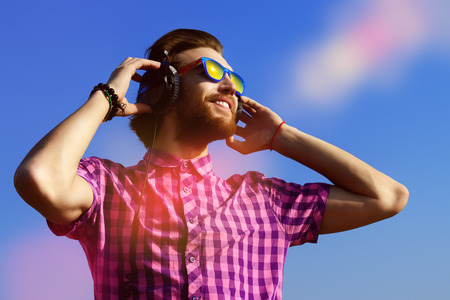 holiday music: Portrait of a dreamy handsome young man listening to music in headphones. Blue sky background. Leisure, summer, vacation.