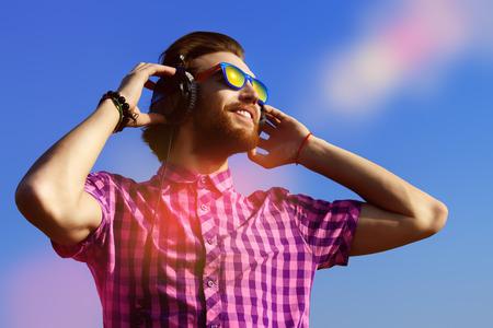 personas escuchando: Retrato de un apuesto joven soñadora escuchando música en los auriculares. Fondo del cielo azul. Ocio, verano, vacaciones.