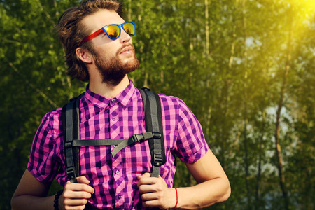 active lifestyle: Modern young man hiking in the forest. Active lifestyle, tourism.