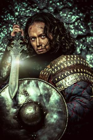 guerrero: Guerrero masculino antigua en la armadura que sostiene la espada y el escudo. Personaje histórico. Fantasía.