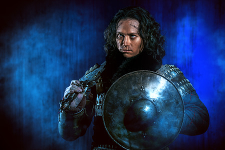 fantasy warrior: Ancient male warrior in armor holding sword and shield. Historical character. Fantasy. Stock Photo