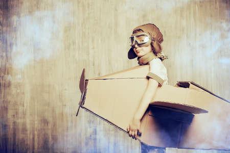 Nette Träumer Junge spielt mit einem Karton Flugzeug. Kindheit. Fantasy, Phantasie. Retro-Stil.