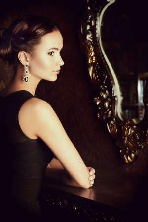 charm temptation: Beautiful elegant lady stands by the mirror in vintage interior. Fashion shot. Stock Photo