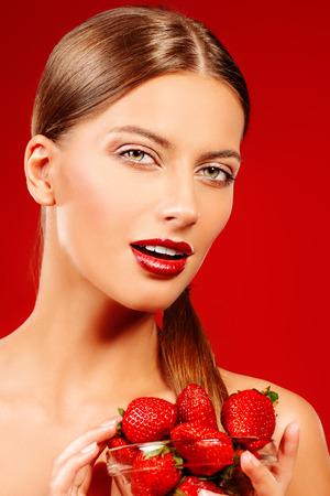 labios sexy: Mujer joven atractiva que come la fresa fresca. Labios sexuales, lápiz labial rojo. Concepto de alimentos saludables. Fondo rojo.