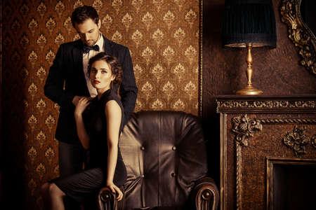 ロマンス: 美しい男と女クラシック ビンテージ アパートで優雅な夜の服。グラマー、ファッション。愛の概念。