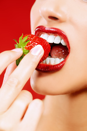 sexy food: Close-up of a sexy female mouth eating fresh strawberry. Sexual lips, red lipstick. Healthy food concept. Red background. Stock Photo