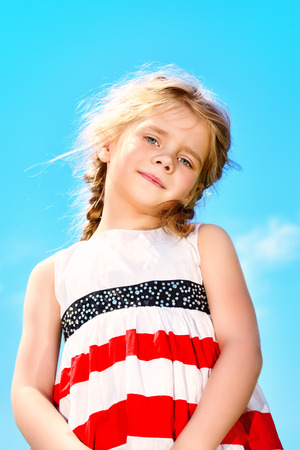 5 year old: Portrait of a cute 5 year old girl on a blue sky background. Happy childhood.