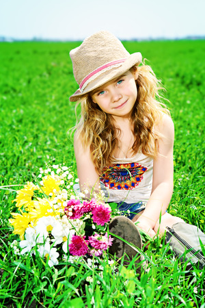 5 year old girl: Cute little girl with charming curly hair on a meadow in summer day. Stock Photo