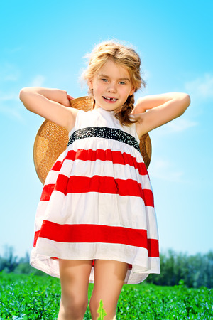 old girl: Charming little girl on a meadow in summer day. Happy childhood. Child fashion.