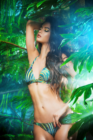 tanned girl: Beautiful sexy woman in bikini among tropical plants. Beauty, fashion. Spa, healthcare. Tropical vacation.