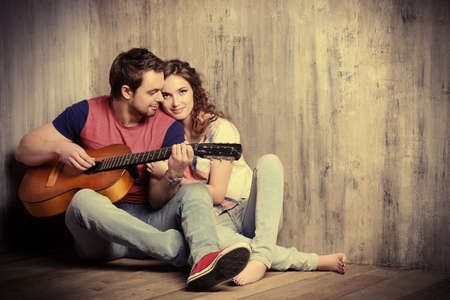 two women hugging: Romantic young man playing the guitar to his beloved girl. Happiness. Love concept. Stock Photo
