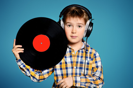 7 year old: Cute 7 year old boy listening to music on headphones and holds vinyl record.