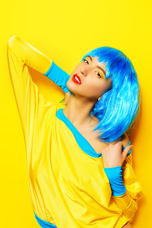 celadon blue: Bright glamorous girl in vivid clothes and a wig alluring over yellow background. Beauty, fashion. Cosmetics, hairtsyle.