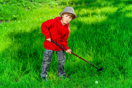 7 years old: Cute 7 years old boy playing golf outdoor. Summer day. Stock Photo