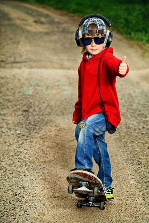 niño en patines: Enfriar niño de 7 años con su patineta en la calle. La Niñez. Summertime. Foto de archivo