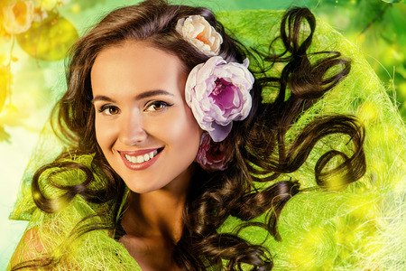 spa beauty: Happy beautiful brunette woman among summer plants and flowers. Beauty, fashion. Spa, healthcare. Tropical vacation. Stock Photo