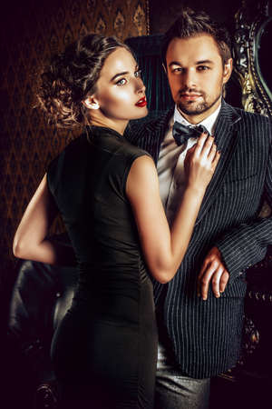 passion couple: Beautiful man and woman in elegant evening clothes in classic vintage apartments.