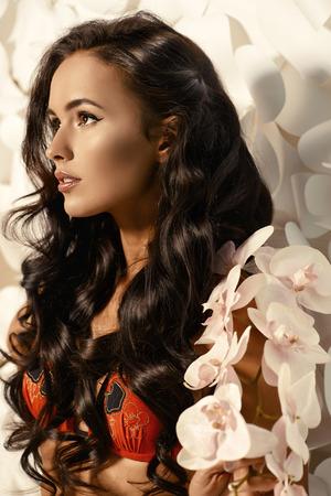 cabello largo y hermoso: Moda foto de una mujer joven hermosa con el pelo largo y hermoso que presenta sobre fondo de flores de papel blanco.