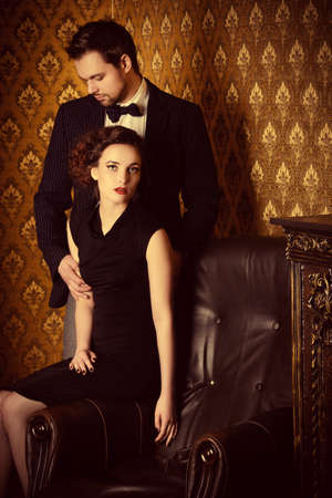 Beautiful man and woman in elegant evening clothes in classic vintage apartments. Glamour, fashion. Love concept.
