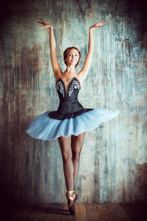 modern ballet dancer: Professional ballet dancer posing at studio over grunge background. Art concept.