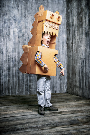 childhood: Little dreamer boy playing with a cardboard dragon, dinosaur. Childhood. Fantasy, imagination.