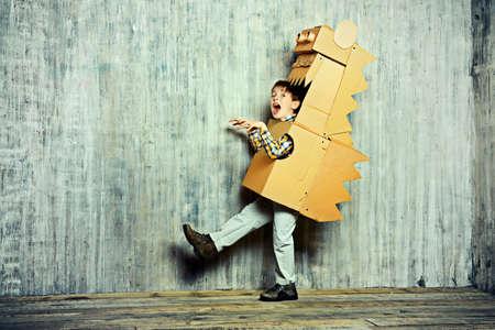 путешествие: Маленький мечтатель мальчик, играя с картонной дракона, динозавра. Детство. Фэнтези, воображение.