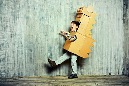 carton: El ni�o peque�o so�ador que juega con un cart�n drag�n, dinosaurio. Ni�ez. Fantas�a, imaginaci�n. Foto de archivo