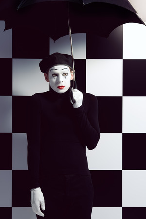 mime: Portrait of a male mime artist standing under umbrella expressing sadness and loneliness. Chess board background.