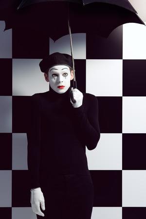 mimo: Retrato de un mimo macho coloca bajo el paraguas que expresan tristeza y soledad. Fondo tablero de ajedrez.