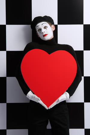 dramatic characters: Portrait of a male mime artist holds large red heart expressing love. Chess board background.