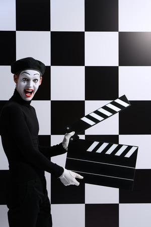 dramatic characters: Movie actor and a mime posing with clapper board with different emotions. Chess board background. Cinema industry. Stock Photo