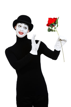 dramatic characters: Emotional male mime artist with red rose performing love. Isolated over white. Stock Photo