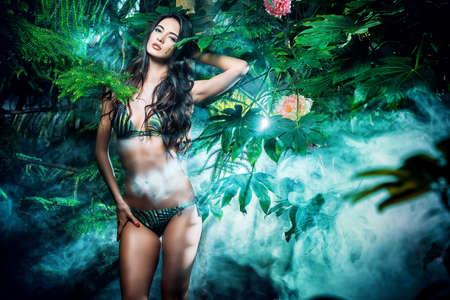 chicas sonriendo: Hermosa mujer sexy en bikini entre las plantas tropicales. Belleza, la moda. Spa, cuidado de la salud. Vacaciones tropicales.