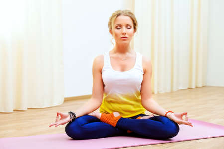 meditation room: Beautiful athletic girl doing yoga exercises indoor. Lotus pose. Meditation. Stock Photo