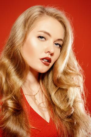 labios sexy: Encantadora mujer joven sonriente en vestido rojo y con el pelo rizado rubio. Belleza, la moda. Cosméticos, maquillaje. Fondo rojo. Foto de archivo