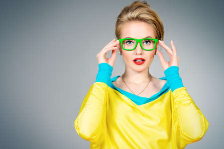 girl glasses: Close-up portrait of a pretty young womanl posing in vivid colourful clothes and glasses. Bright fashion. Optics, eyewear. Studio shot. Stock Photo